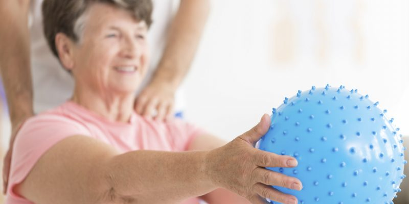 Smiling senior woman exercising with blue ball during physiotherapy